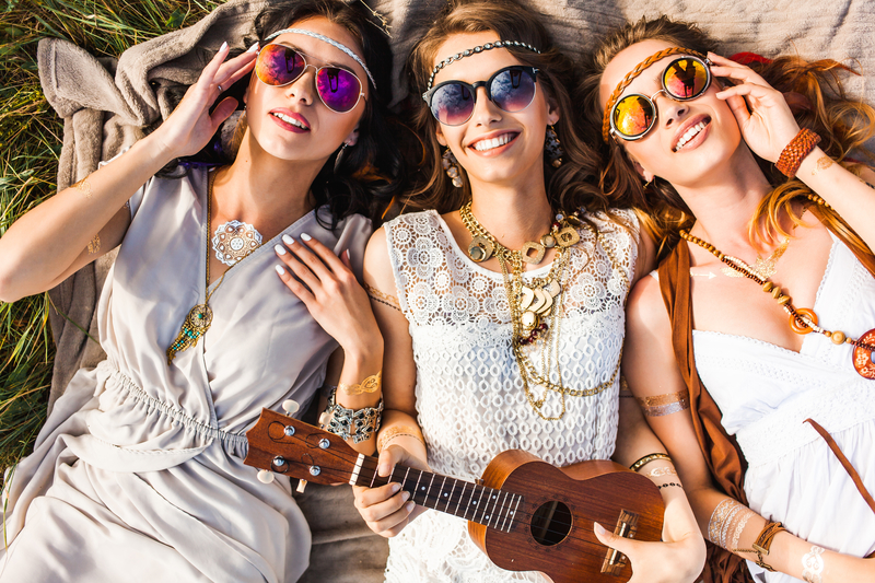 Three attractive girls lying on the ground, laughing and wearing sunglasses