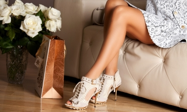 Woman sitting on couch wearing designer shoes