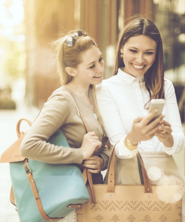 Two women walking down the street looking at a cell phone