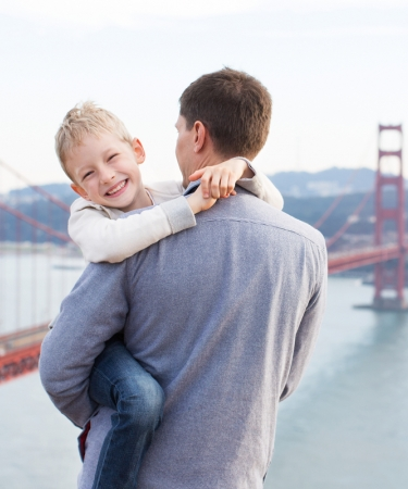 Man holding his son by the Golden Gate Bridge - a San Francisco Attraction