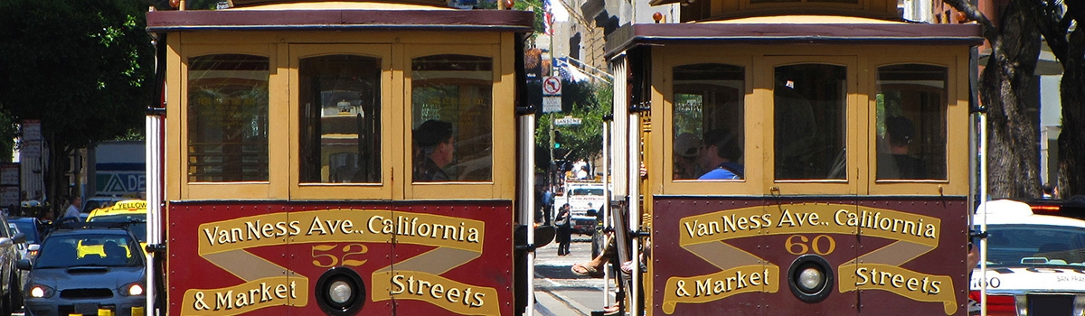 Two red cable cars on a street in San Francisco