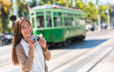 Woman taking a photo with a San Francisco cable car in the back