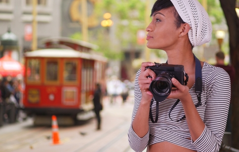 Woman holding a camera with a streetcar in the background