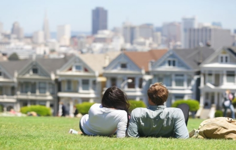 Couple relaxing on a hill in San Francisco overlooking a row of houses