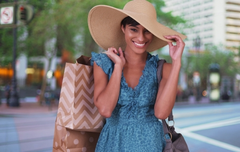 Woman in a large hat carrying shopping bags