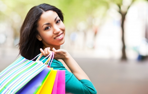 Woman holding colorful shopping bags over her shoulder