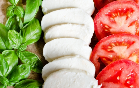 Neat rows of basil, mozzarella, and tomatoes