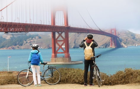 Couple on bicycles stopping to look at the Golden Gate Bridge - a San Francisco Attraction